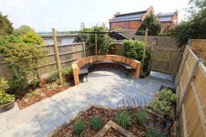 View of bespoke curved seating area made with Oak cladding and Millboard seating.