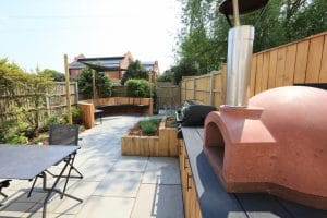 Image of Summer Entertaining Garden with curved seating area, Pizza oven, BBQ and Oak planters